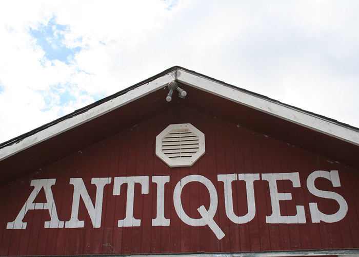 Top of a red building with the word 'Antiques' painted on it