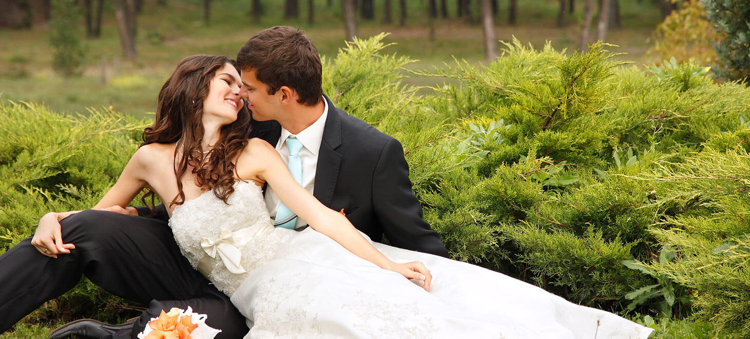 Bride and groom sitting in the grass kissing