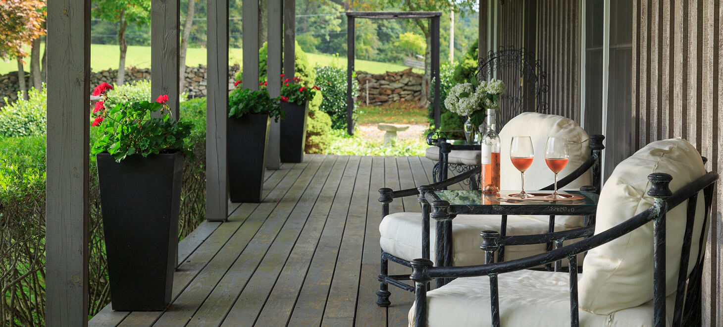 Mews Cottage porch with chairs and table with wine
