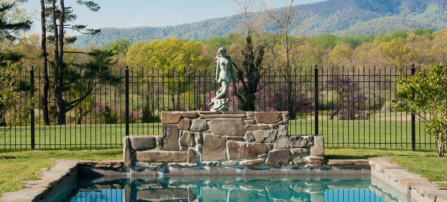 an overlook of a large pool with a small Greek-style statue at the end