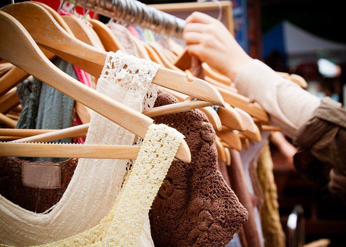 Person shopping through a rack of clothes