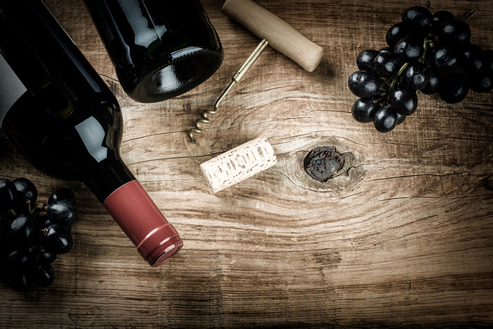 Wine bottles, corkscrew and grapes on a wooden table