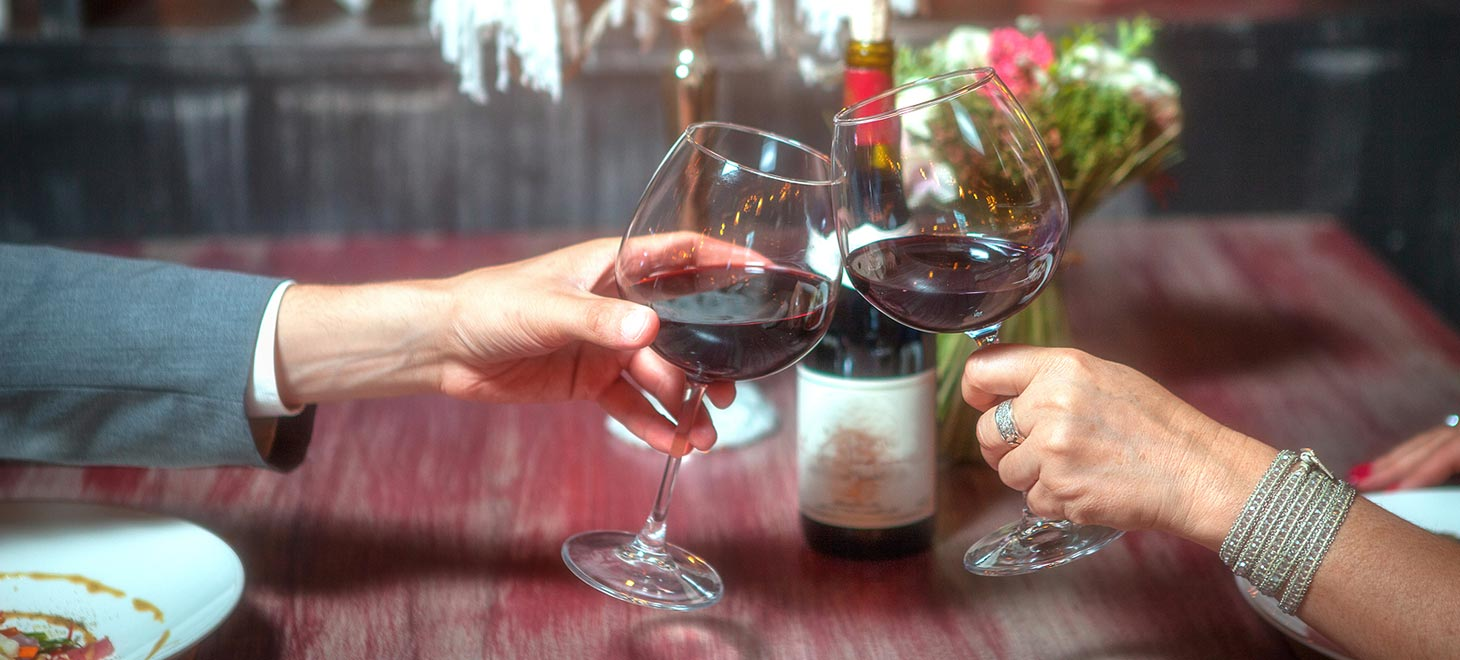 Couple dining, chinking glasses with red wine