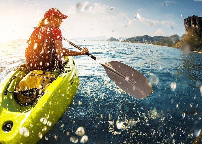Woman kayaking and splashing water