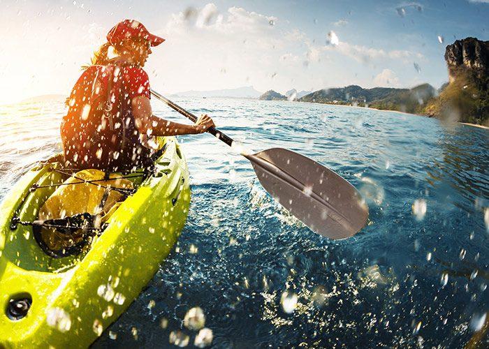 Woman kayaking and splashing water