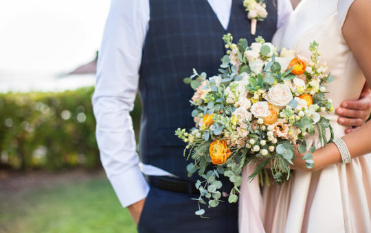 bride and groom holding a bouquet of flowers