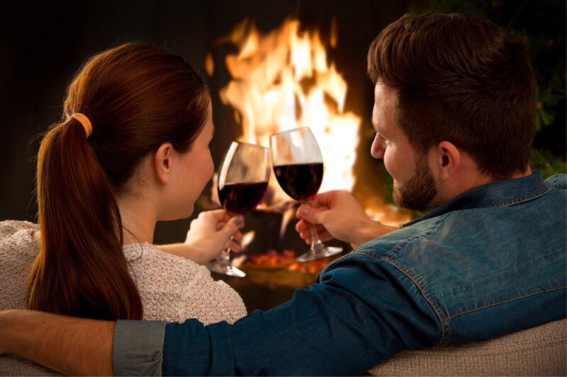 couple in front of a fireplace with wine