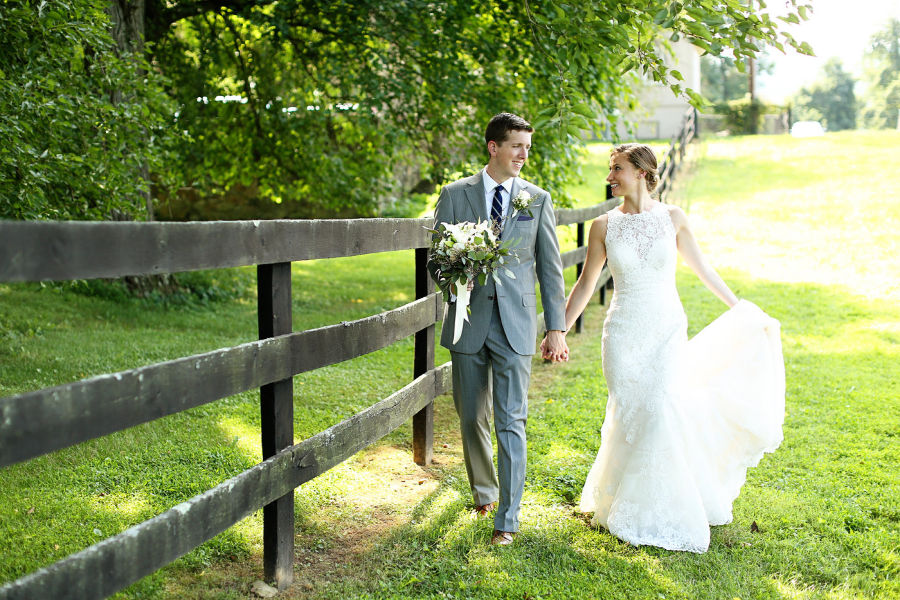 Husband and wife celebrating their virginia wedding in wine country, standing by a fence