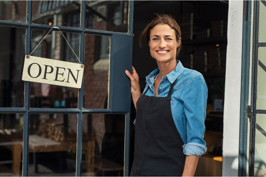 Business owner in front of business with open sign