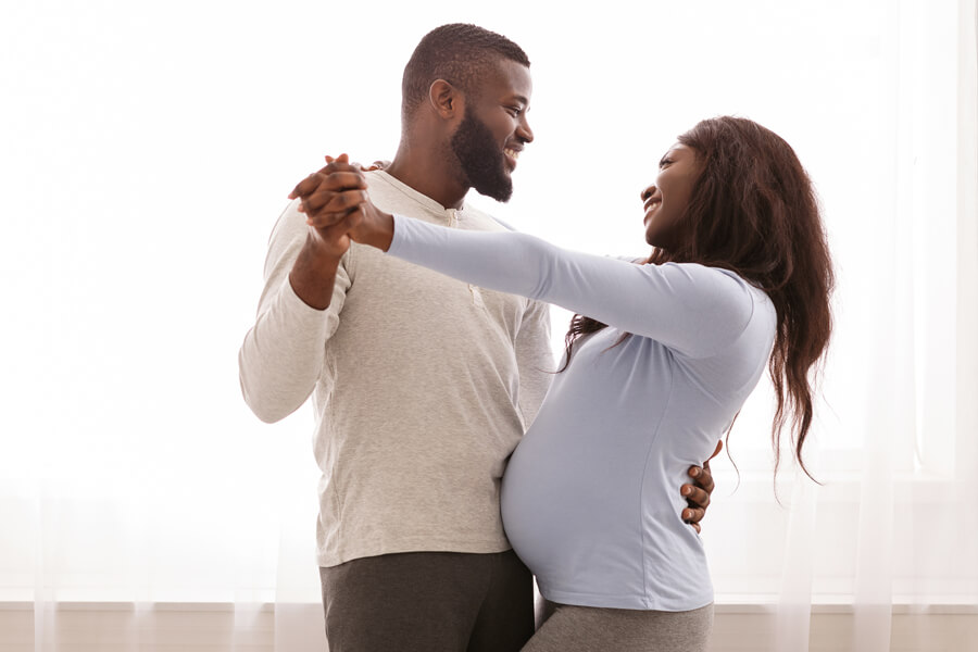 Happy pregnant couple dancing in hotel room
