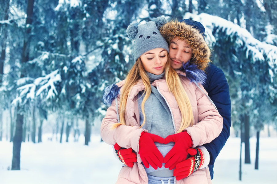 Pregnant couple in love in the woods and snow