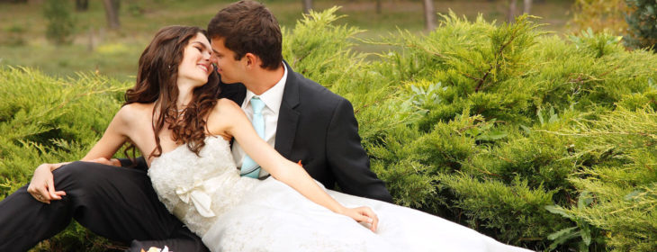 Bride and groom sitting in the grass kissing at on of the best places to elope in Virginia